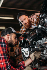 handsome young mechanics repairing motorcycle together at garage