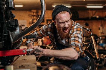 repair station worker trying to fix bike at garage and shouting to colleague