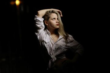 studio portrait of a blond woman on black background