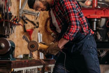 young repair station worker using electric circular saw at garage