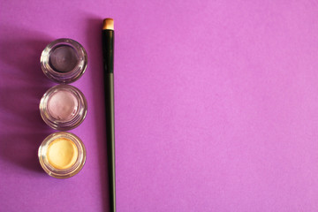 Group of three eye shadows, make up brush, violet background, free copy space