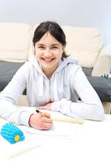 Odrabianie zadań domowych. Uśmiechnięta dziewczynka uczy się do egzaminu.