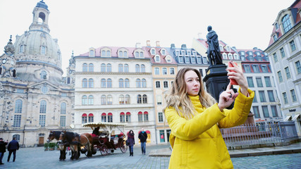 Exquisite Young woman holding gadget and talking on Internet with friend, waving hand at camera of smartphone and showing architecture of old European city Dresden. Young European-looking woman with