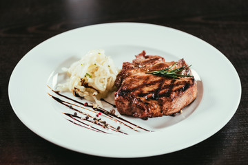 delicious grilled juicy steak with rosemary and sauce on plate