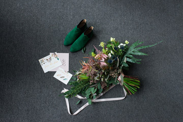Green bridal shoes, rich green wedding bouquet with pink ribbons and a wedding complimentary lying on a grey floor