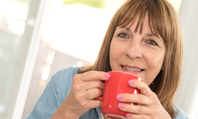 Mature woman during coffee break at home