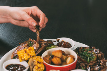 cropped shot of person eating delicious grilled chicken with roasted vegetables in restaurant
