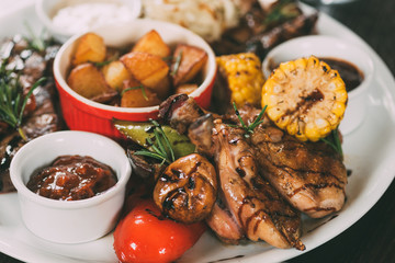 tasty grilled chicken with fried potatoes, corn, mushrooms and sauce on plate