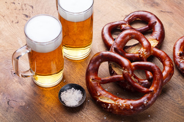 Beer, salted pretzels, potato chips on wooden background.