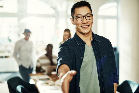Young Asian businessman standing in an office extending a handshake