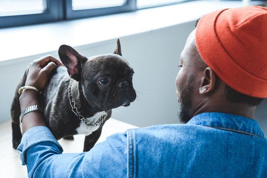 African american man cuddling cute French bulldog
