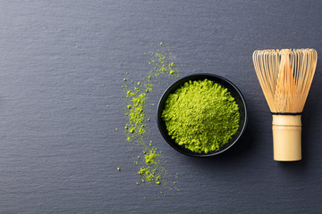 Matcha, green tea powder in black bowl with bamboo whisk on slate background. Top view. Copy space