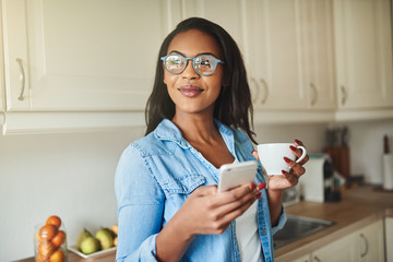 Smiling young African woman drinking coffee and using a cellphone