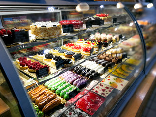 A lot of different types of cake in glass cabinet story cafe.
