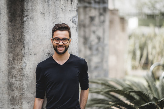 Handsome smiling bearded hipster guy in glasses and t-shirt is leaning on the concrete wall behind him; portrait of cheerful young Brazilian man outdoors with copy space place for your logo or text