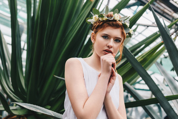 portrait of beautiful elegant red-haired girl in floral wreath looking at camera