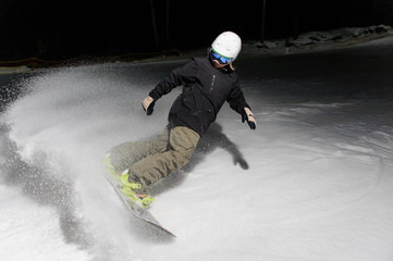 Young snowboarder riding down the mountain slope at night
