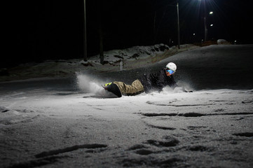 Active snowboarder riding down the mountain slope at night