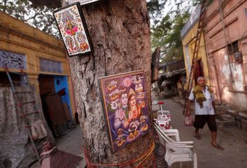 A man walks past pictures of Hindu deities tied to a tree in the old quarters of Delhi