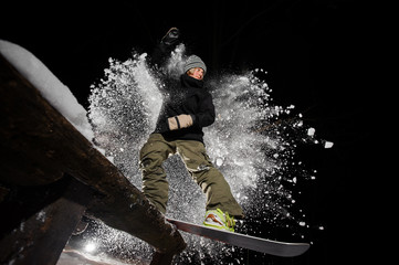 Active female snowboarder riding down the mountain slope at night