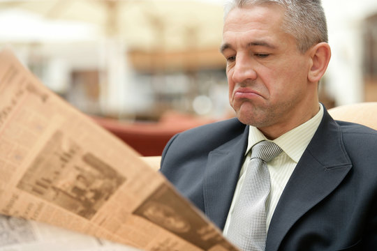 Businessman reading bad news on a business newspaper