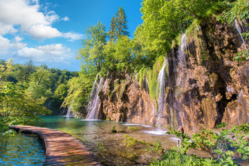Foto op Aluminium Watervallen Incredibly beautiful fabulous magical landscape with a bridge near the waterfall in Plitvice, Croatia (harmony meditation, antistress - concept)