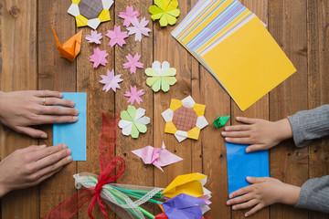 折り紙を折る親子の手