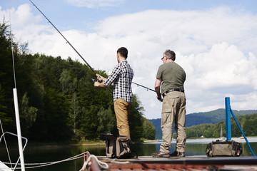 Tuinposter Ontspanning Rear view of men fishing