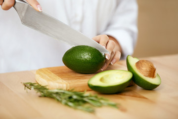 Diet. Female Hands Cutting Avocado In Kitchen.