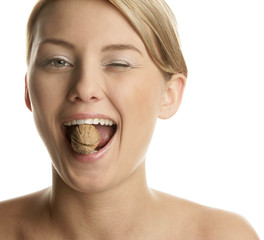 Woman cracking walnut with her teeth