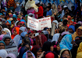 """Muslim women hold placards during a protest rally against what they say is a bill that aims at prosecuting Muslim men who divorce their wives through the """"triple talaq,"""" or instant divorce, in Kolkata"""