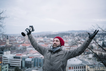 Man with beanie and beard shouts camera in hand city background.
