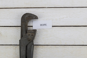 pipe wrench compresses a piece of paper with an inscription Hope.