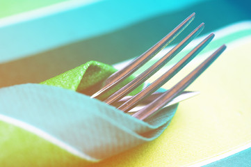 Fork and knife in a bright napkin close up on a table, soft focus. Tableware