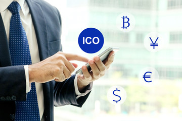 Businessman hand using smartphone with ICO, Initial Coin Offering, icon on a virtual screen. Cryptocurrency, Bitcoin and ICO Digital Electronic Trade Market Stock Index concept.