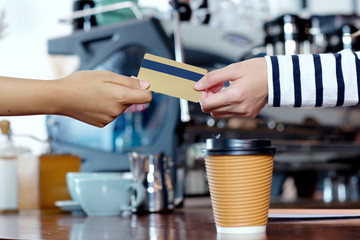 Customer paying coffee by credit, debit electronic card at cafe counter, food and drink business concept