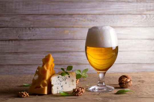 Beer and cheese. Glass of beer with cheese, walnuts and basil on wooden background. Ale and food concept