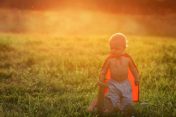 Little prince kid in costume hero. Small boy king outdoors sunset ray light summer. artistic image. Cute caucasian baby dressed image playing hero,knight. Silhouette small kid warrior. Copyspace.