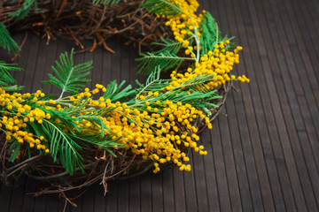 Wreath of mimosa with eggs on a brown background