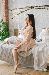 A young girl sits on a bed in a luxurious negligee
