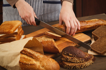 Woman cutting bread on wooden board