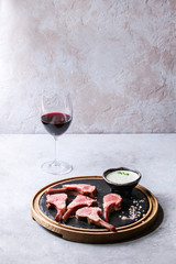 Grilled sliced rack of lamb with yogurt mint sauce served with green salad young beetroot leaves, glass of red wine, pink salt on round wooden slate board over grey texture table. Copy space