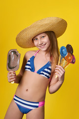 Cute girl wearing swimsuit holds in hand image ice cream. Cheerful young woman teenager loves summer. Beautiful caucasian girl slender body posing in studio. Concept, fashion, bikini.