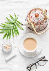 Tea with milk. Masala tea, teapot, cosmetics, lipstick, facial oil, glasses, green leaf flower on light background, top view. Cozy women's still life. Flat lay