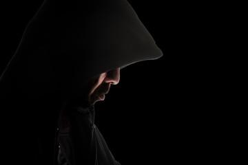 Man in hood / Hooded man in shadow on black background.