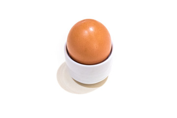 boiled egg in ceramic cup on white background