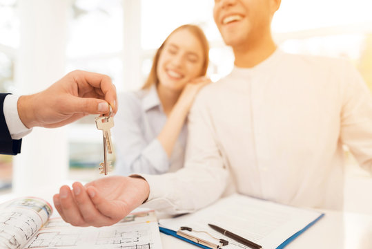 Young couple in a meeting with a realtor. Guy and girl make a contract with realtor buying property.