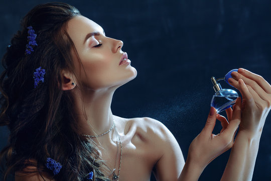 Close up studio portrait of young beautiful woman holding, spraying, using perfume in blue bottle. Model with nude makeup, greek braid hairstyle, posing on dark background. Copy, empty space for text