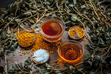 In de dag Kruiden Close up of fenugreek tea with honey,lemon,sugar and fenugreek seeds on a wooden surface in dark Gothic colors.It helps to soothe menstrual cramps, lower blood sugar, promote proper digestion, etc.