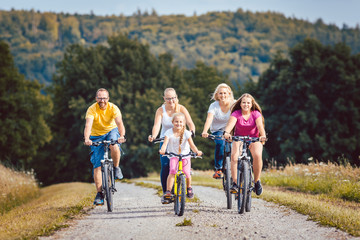 Family riding their bicycles on afternoon in the summer countryside